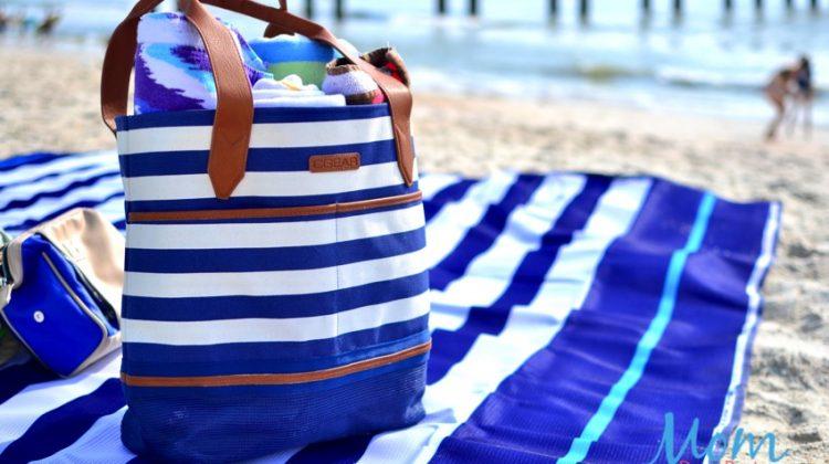 beach bag and beach blanket on sand