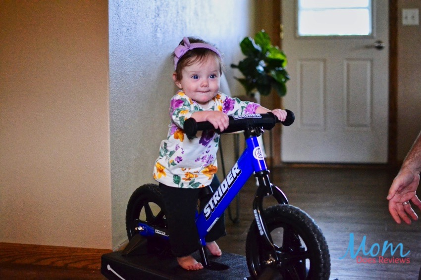 baby on strider bike with base