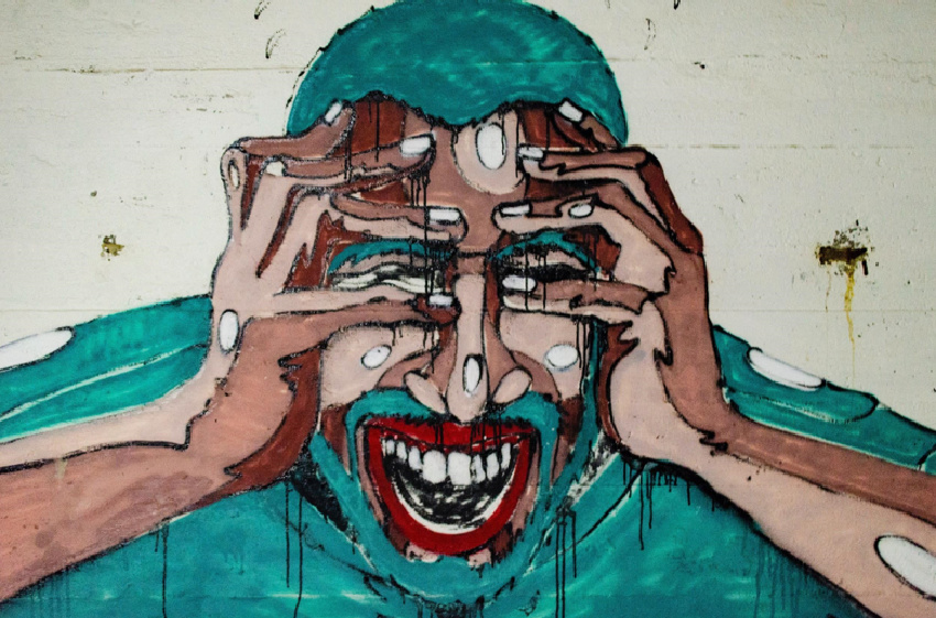 Artistic picture of stressed person holding their face and head in their hands.