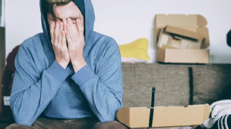 Man in blue hoodie holding his face in his hands.